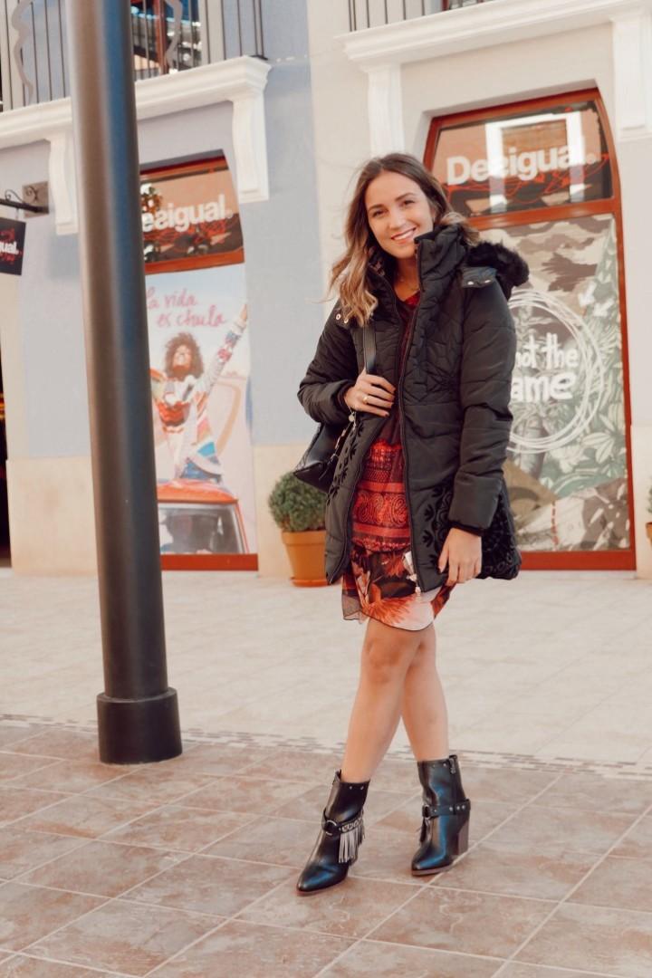 Look de vestido con botas negras y abrigo de Desigual